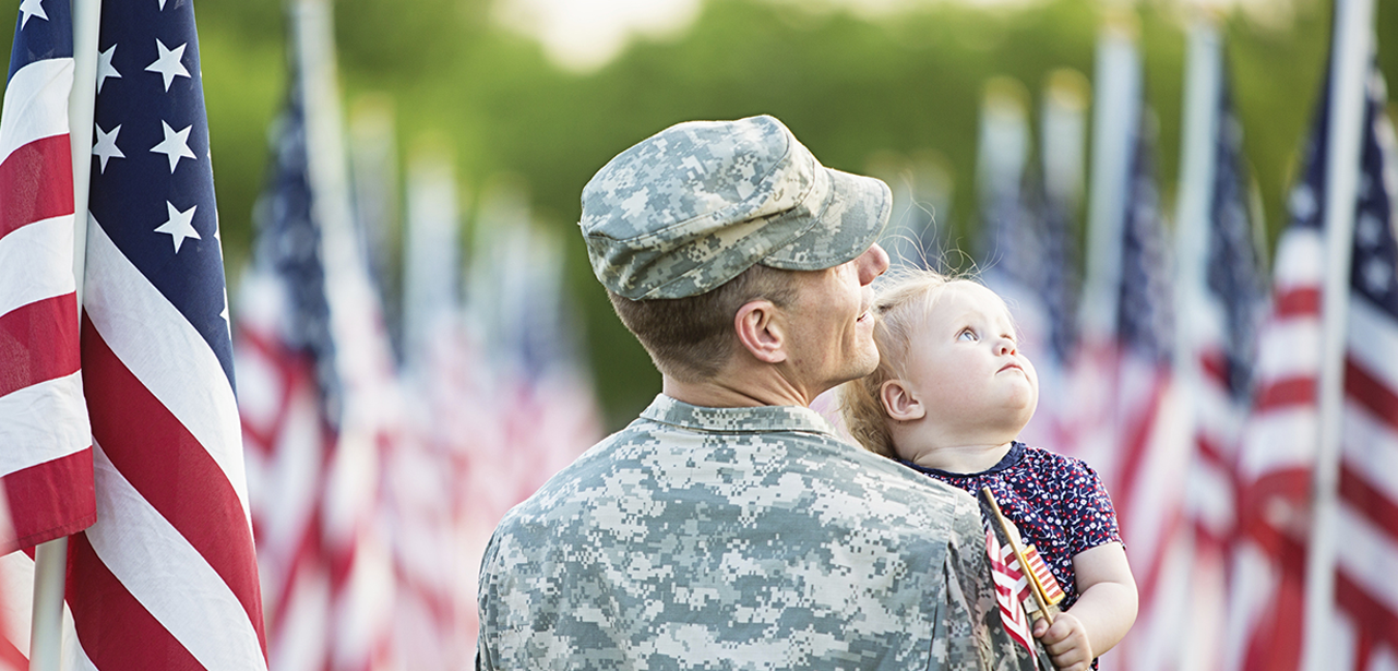 Military man holding his daughter and looking at the American flags all around them