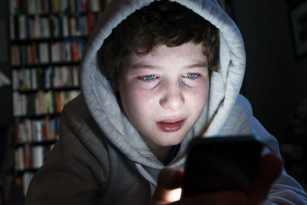 image of a boy on a cell phone to demonstrate cyber bullying