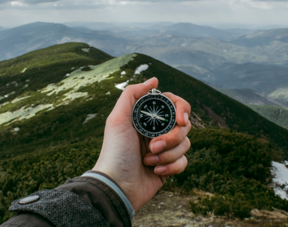 hand holding a compass in front of a mountain