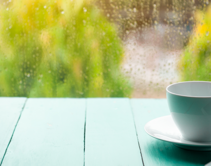 a tea cup on a table in front of a rainy window