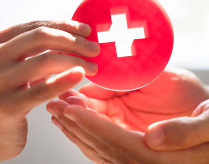 First aid symbol being handed from one to another