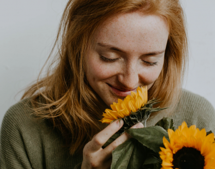 Photo of woman smelling sunflower