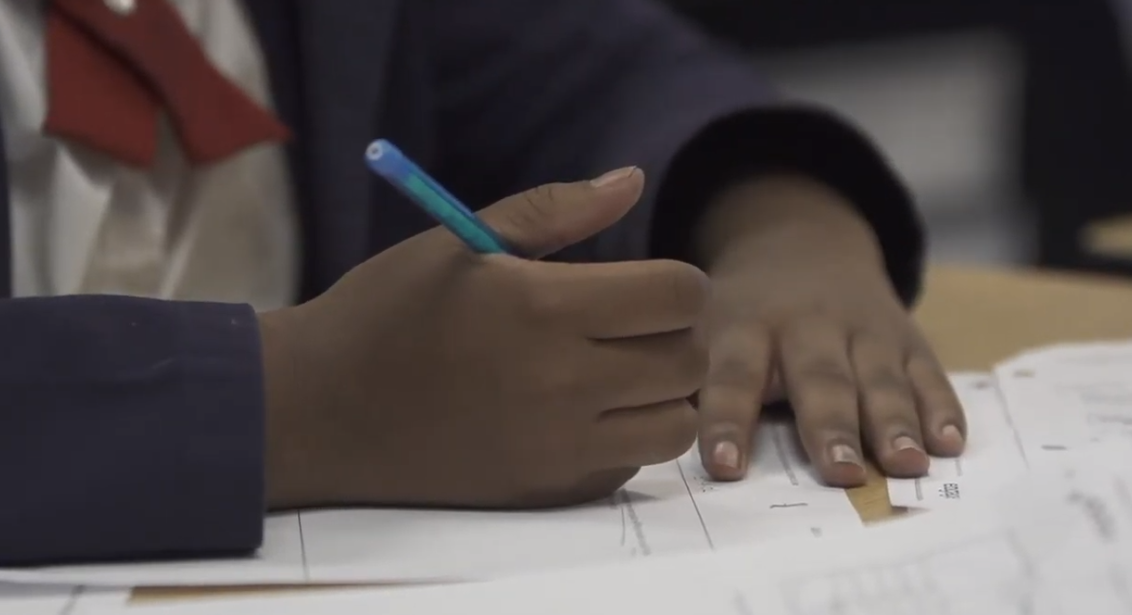 image of a boys hands holding a pencil and working on homework