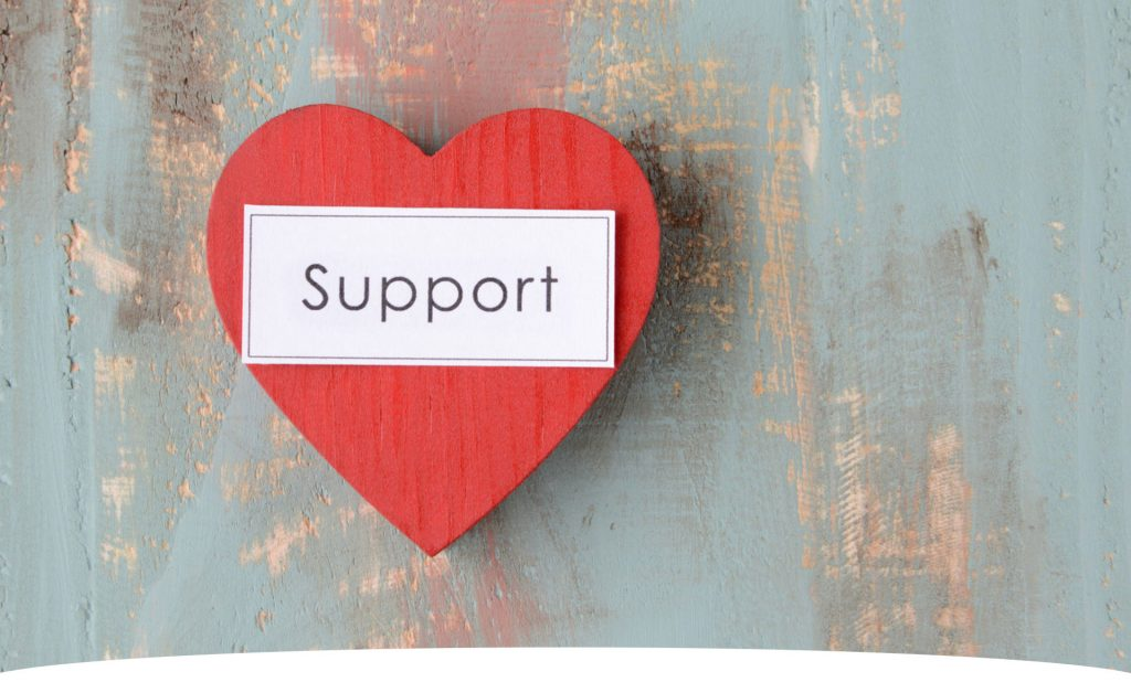 """a red wooden heart with the word """"support"""" on top of it"""