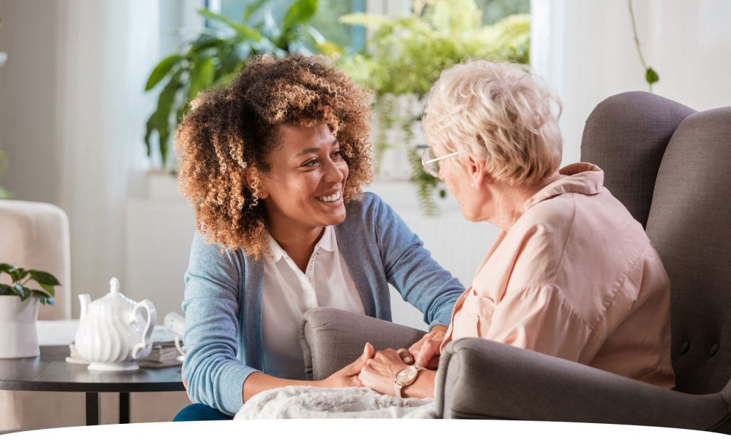 home care worker holding the hand of an elderly woman